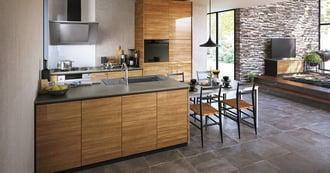 グレーの床とベージュの壁に、木目扉のキッチンとリビング収納をコーディネート